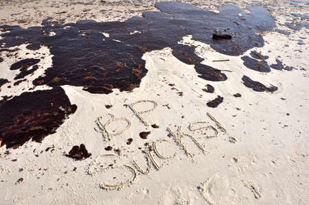 BP oil spill on Gulf of Mexico beach.  BP SUCKS Written in sand.