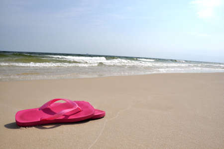 Pair of flip flops on beach with copy space.