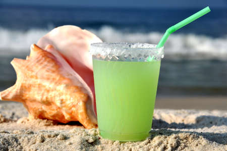 Margarita on beach with seashell in background.