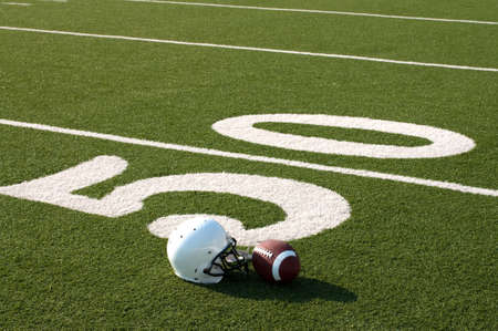 American football and helmet on field next to 50 yard line. photo