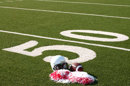 fall line: American football, helmet, and pom poms on field next to 50 yard line. Stock Photo
