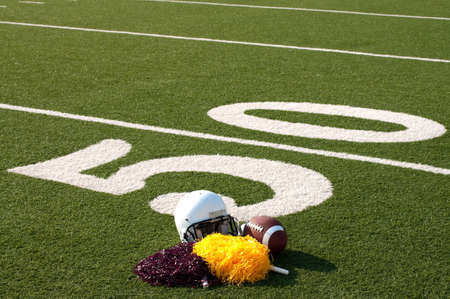 yardline: American football, helmet, and pom poms on field next to 50 yard line. Stock Photo