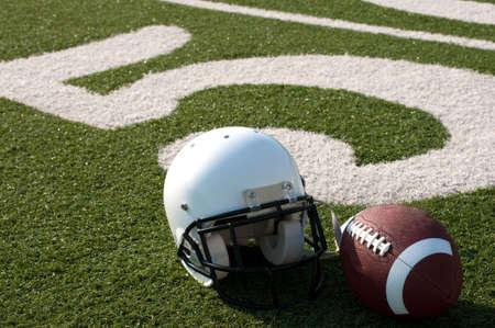 yardline: American football and helmet on field next to 50 yard line.