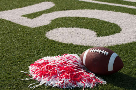 American football and pom poms on field next to 50 yard line. Stock Photo - 7625467
