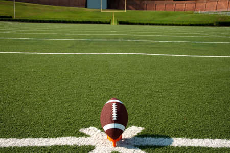 American football on tee on field with goal post in background. Stock Photo