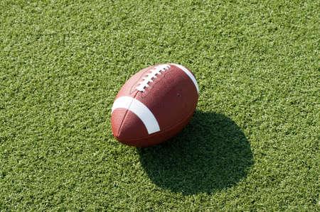 アメリカン ・ フットボール午後の影が付いたフィールドに座っています。 写真素材