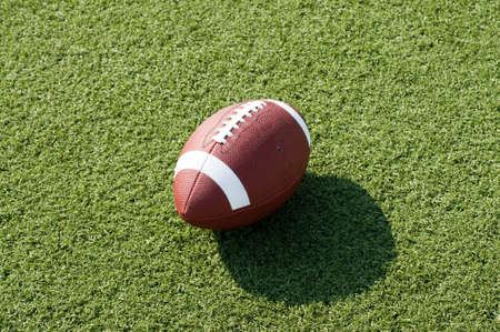 American football sitting on field with afternoon shadow showing. photo