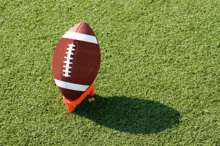kickoff: American football on tee sitting on field with afternoon shadow showing. Stock Photo