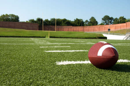 Closeup of American football on field with goal post in background photo
