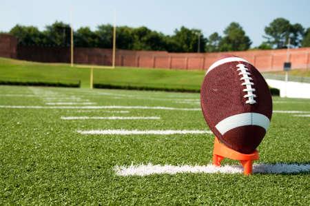 campo di calcio: Closeup di football americano su tee con obiettivo post in background