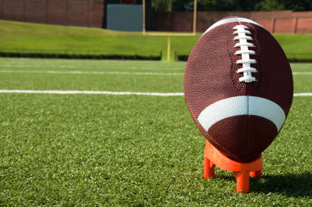 Closeup of American football on tee with goal post in background Stock Photo - 7625435