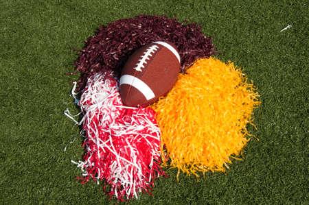 pom poms: American football and pom poms on field.