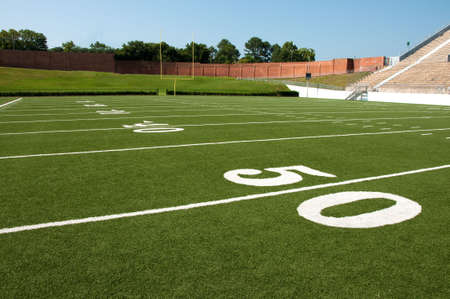sideline: American football field with goal post in background.