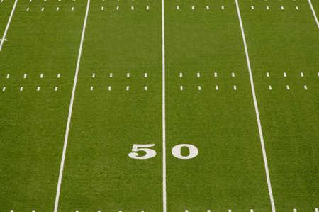 Empty American football field showing 50 yard line.