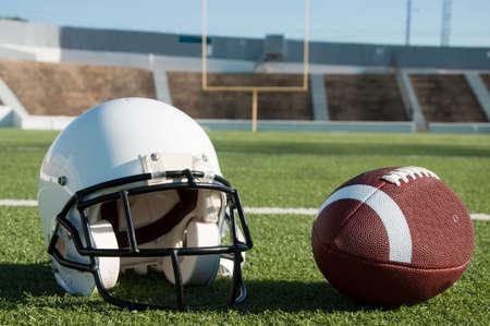 campeonato de futbol: F�tbol americano y el casco en campo con el objetivo puesto en segundo plano.  Foto de archivo