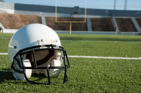 American football  helmet on field with goal post in background.