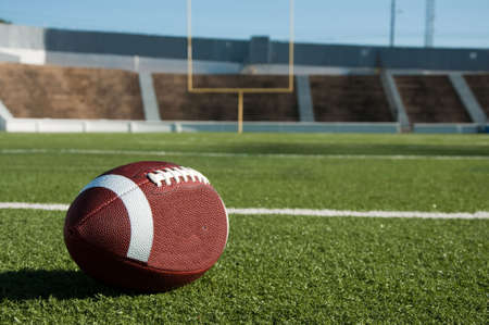 american football background: American football on field with goal post in background. Stock Photo