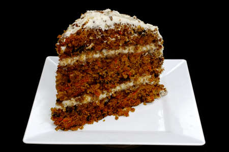 Segment van wortel taart op witte plaat.  Geïsoleerd op zwarte achtergrond. Stockfoto