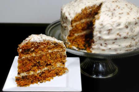 Plak van wortelcake op witte plaat met gehele cake op achtergrond. Stockfoto