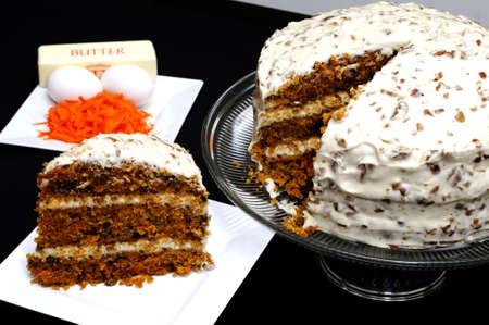 Segment van wortel taart op wit bord met hele taart en ingrediënten in de achtergrond.