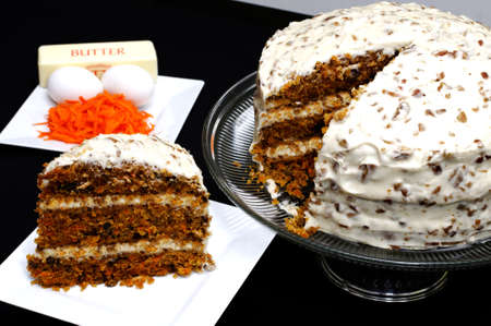 Slice of carrot cake on white plate with whole cake and ingredients in background. Banco de Imagens