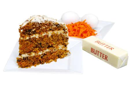 Segment van wortel taart op witte plaat met ingrediënten in de achtergrond. Geïsoleerd op een witte achtergrond met uitknippad. Stockfoto