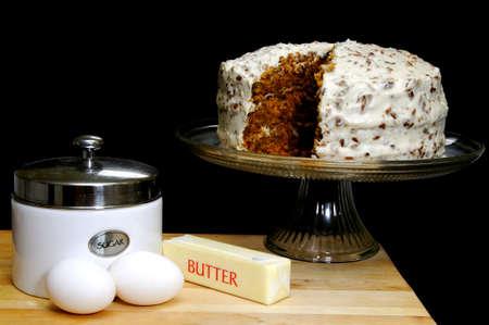 Carrot cake met ingrediënten.  Suiker, eieren, en de boter in de voorgrond.