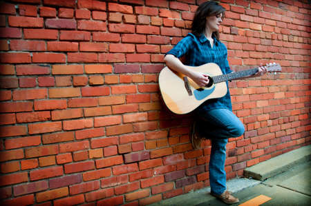 Young female standing in front of  brick wall and playing guitar.