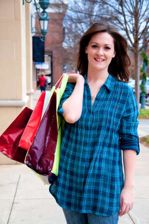Attractive young brunette walking down sidewalk and holding shopping bags while on shopping spree