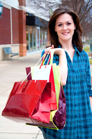Attractive young female holding shopping bags while on shopping spree.