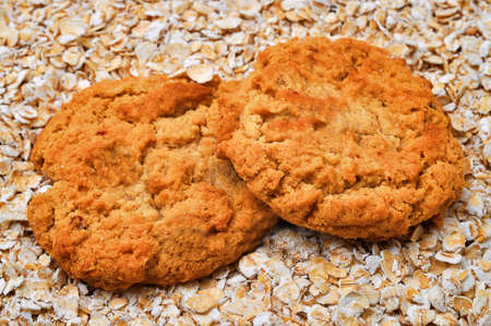 oatmeal: Two oatmeal cookies on bed of oatmeal. Stock Photo