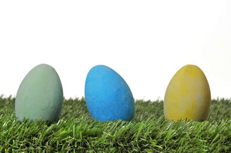 Three Easter eggs on grass on white background. photo