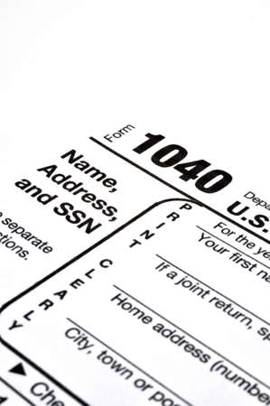 Closeup of IRS form 1040 on white background with ink pen and coffee.