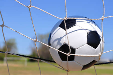 Closeup of soccer ball in net with goal in background.