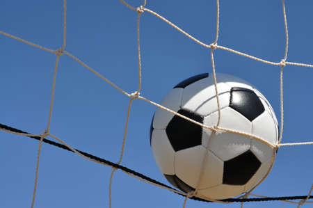 Closeup of soccer ball in net with copy space.