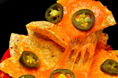 nacho chip: Closeup of nachos with jalapeno pepper slices.  Isolated on black background. Stock Photo