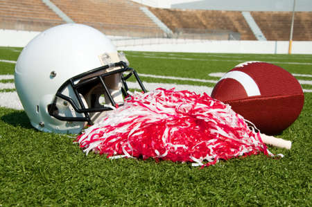 American football, helmet, and pom poms on field in stadium. photo