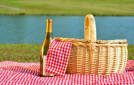 wei?wein: Picknick-Korb und Flasche Weisswein auf rot karierte Decke neben See.