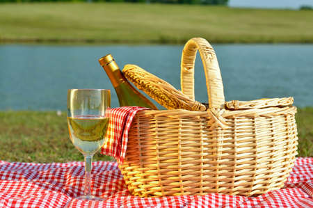 Bottle of white wine in picnic basket with glass of wine beside it.  Red gingham blanket and napkin with lake in background.