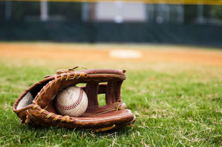 outfield: Old baseball and glove on field with base and outfield in background. Stock Photo