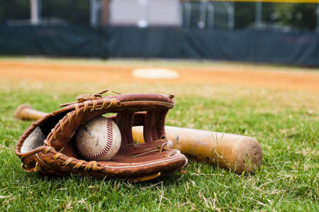 baseball: Old baseball, glove, and bat on field with base and outfield in background.