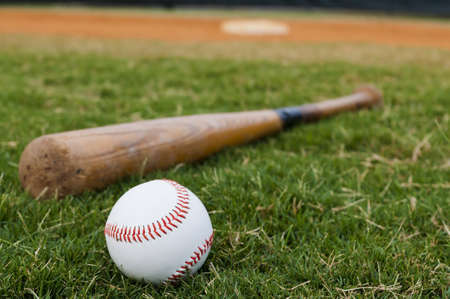 Baseball and old bat on field with base and outfield in background. Stock Photo - 9755725