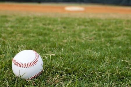 pelota de beisbol: B�isbol en el campo base y el outfield en segundo plano.