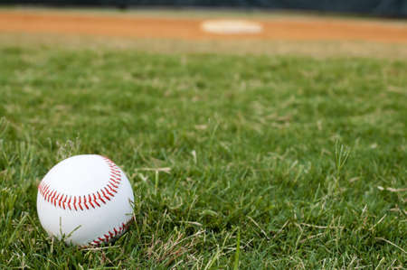 baseball ball: Baseball on field with base and outfield in background.