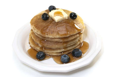 Pancakes with blueberries, syrup, and butter isolated on white background.
