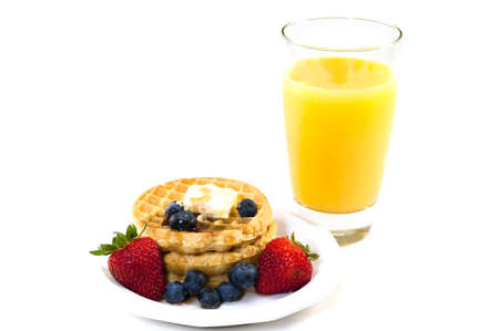 Stack of waffles, blueberries, and strawberries syrup, butter, and orange juice.   Isolated on white background.
