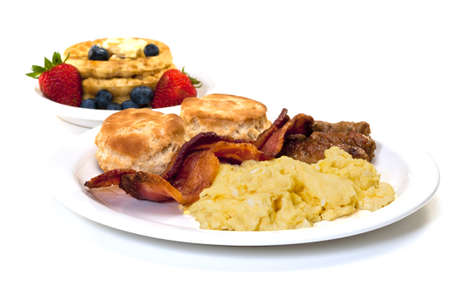 Scrambled eggs, bacon, link sausage, biscuits,  and waffles with strawberries and blueberries.  Isolated on white background.