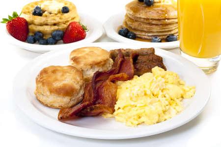 scrambled eggs: Placa de desayuno con huevos revueltos, bacon y galletas de suero de mantequilla.  Waffles, pancakes y jugo de naranja en segundo plano.  Aisladas sobre fondo blanco.
