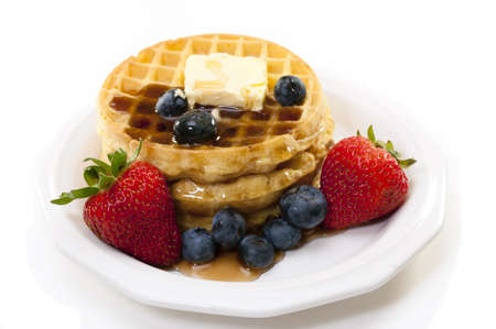 Waffles, strawberries, blueberries, and butter.   Isolated on white background. Zdjęcie Seryjne