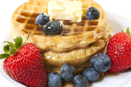 Closeup of waffles, strawberries, blueberries, and butter.   Isolated on white background.